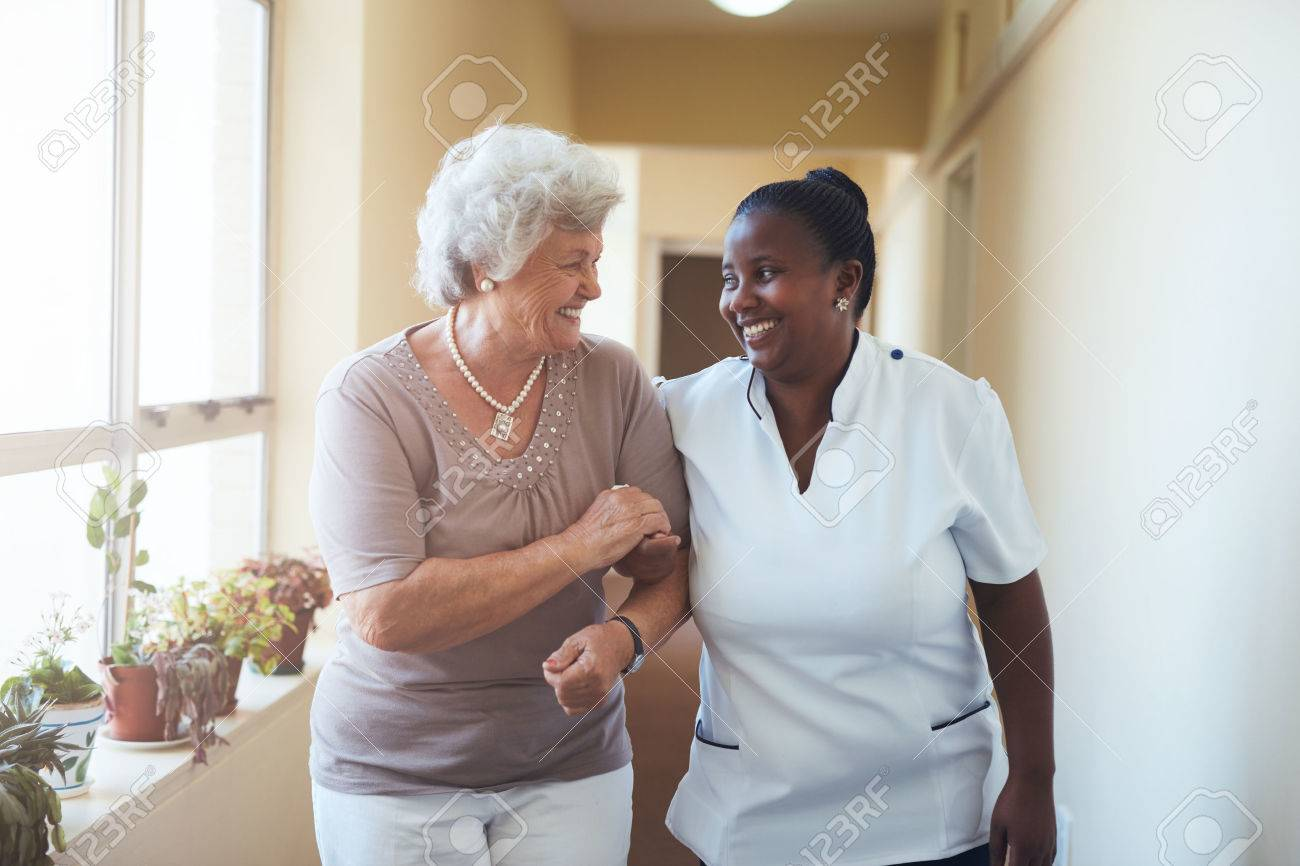 Portrait of smiling home caregiver and senior woman walking together through a corridor. Healthcare worker taking care of elderly woman. Stock Photo - 57027662