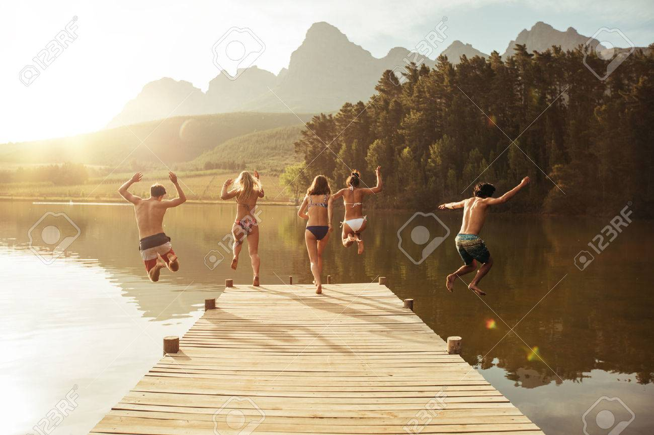 Group of young people jumping into the water from a jetty. Group of friends jumping from pier in the lake on a sunny day. Stock Photo - 58559450