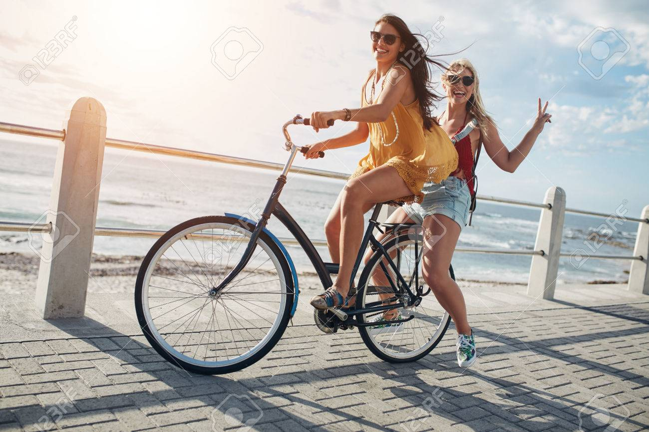 Two stylish young female friends on a bicycle along seaside. Best friends enjoying a day on bike. - 58767243