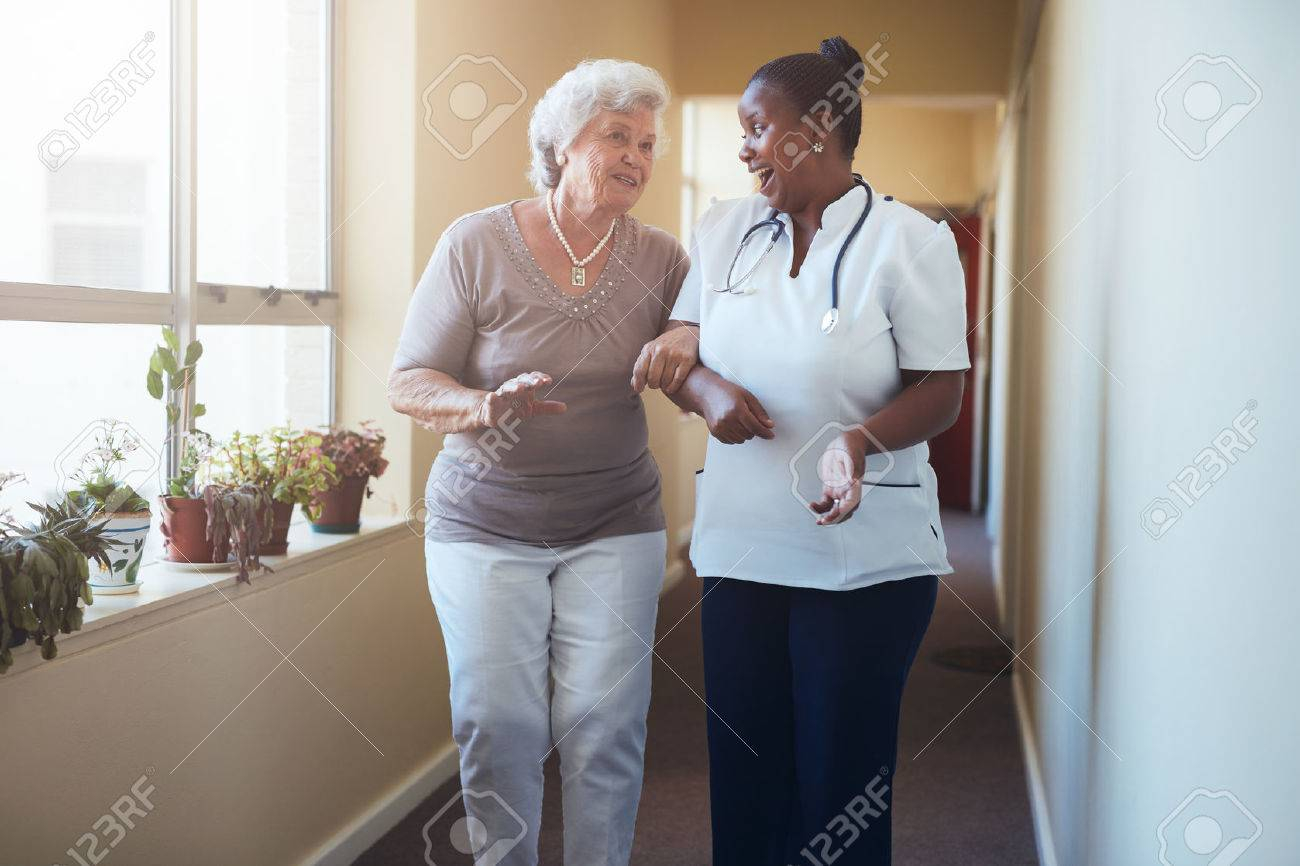 Portrait of happy healthcare worker walking and talking with senior woman. Elder woman gets help from nurse for a walk through nursing home. Stock Photo - 59500341