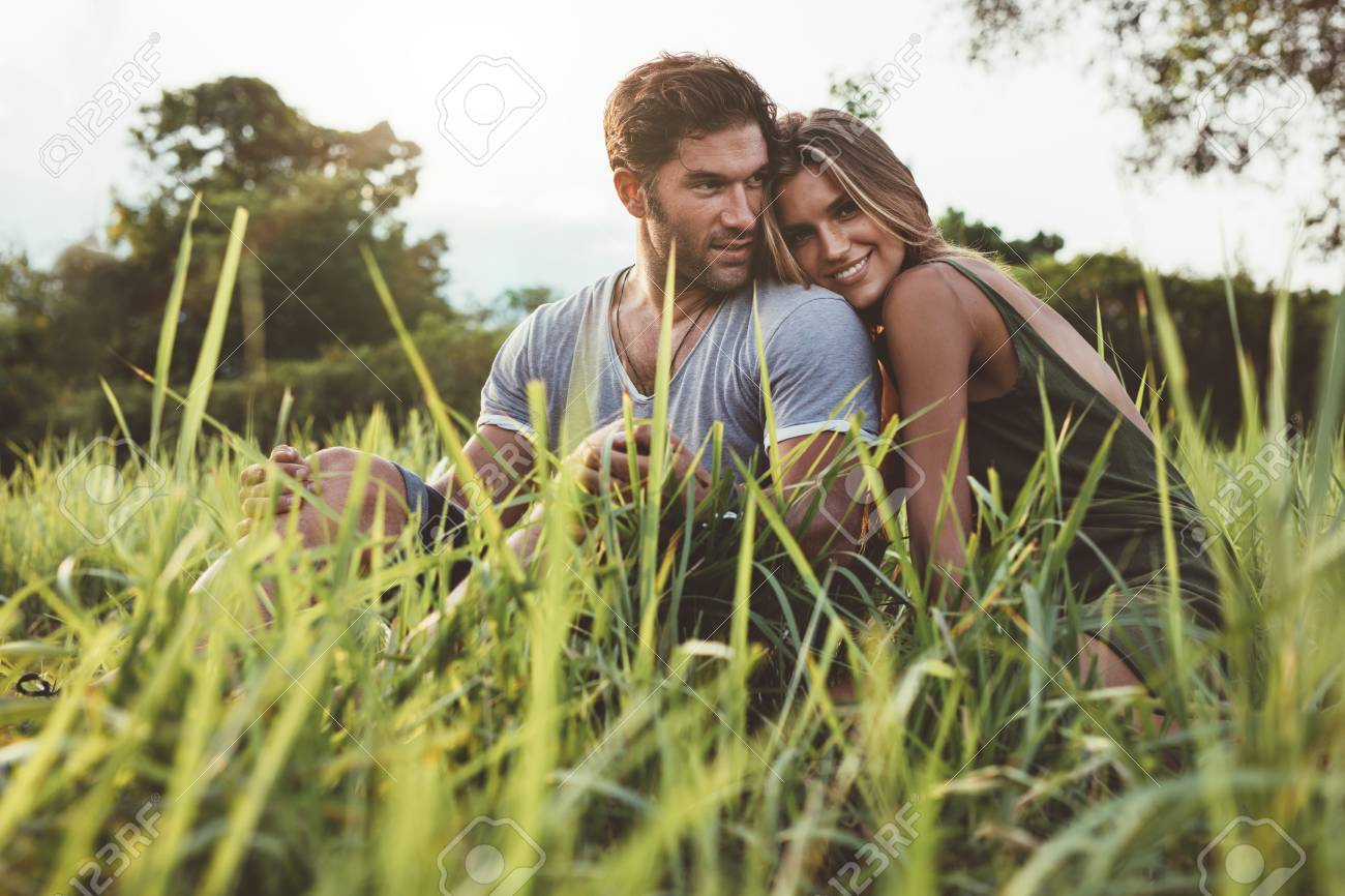 Shot of affectionate young couple enjoying a day outdoors. Man and woman sitting on grass field on a summer day. - 60257491