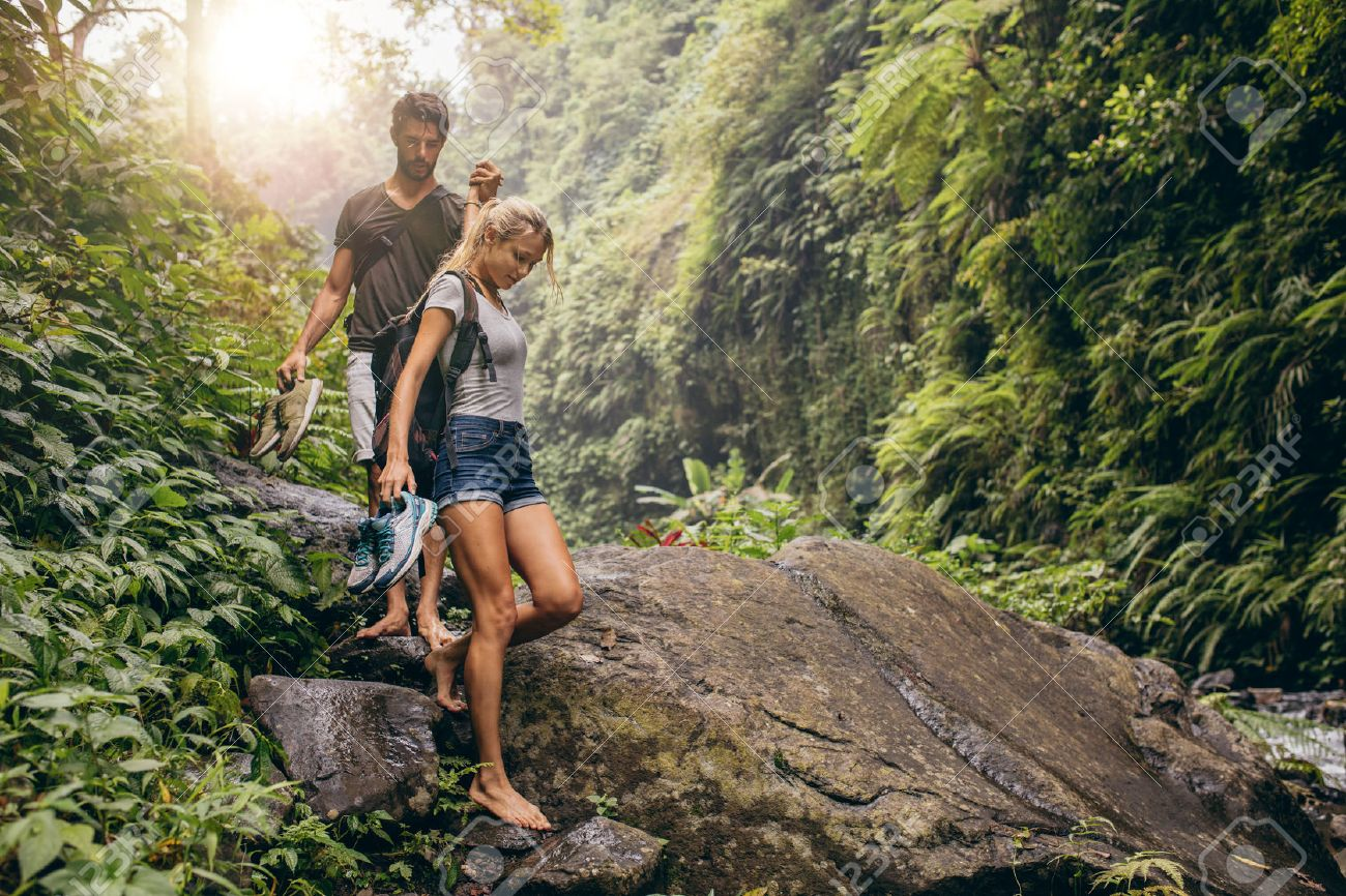 Shot of young couple walking through the mountain trail. Man and woman hiking on mountain trail barefoot. - 60178748