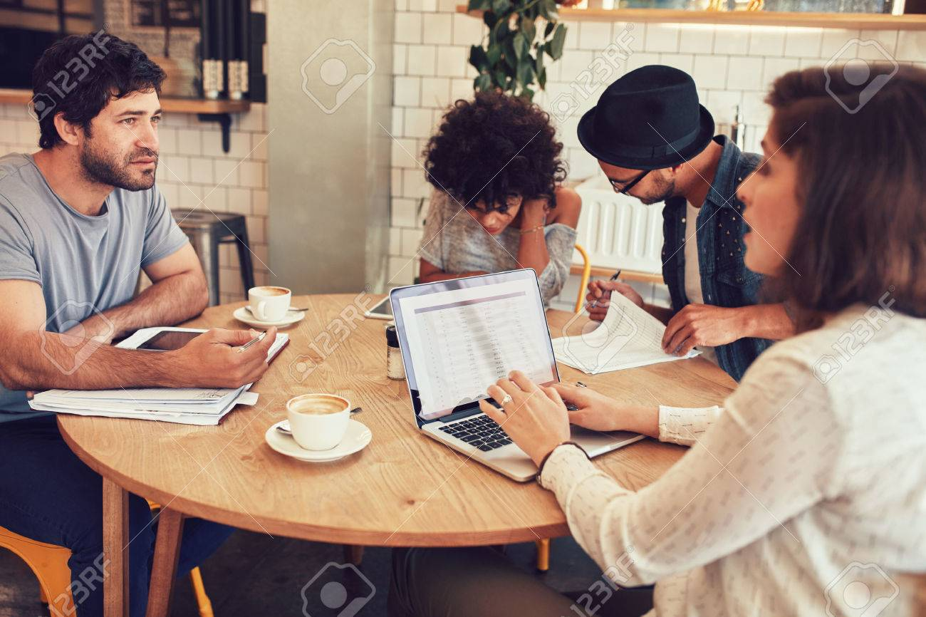 Team of creative people sitting at a cafe with some documents and laptop. Young men and women in coffee shop for business meeting. - 60417858
