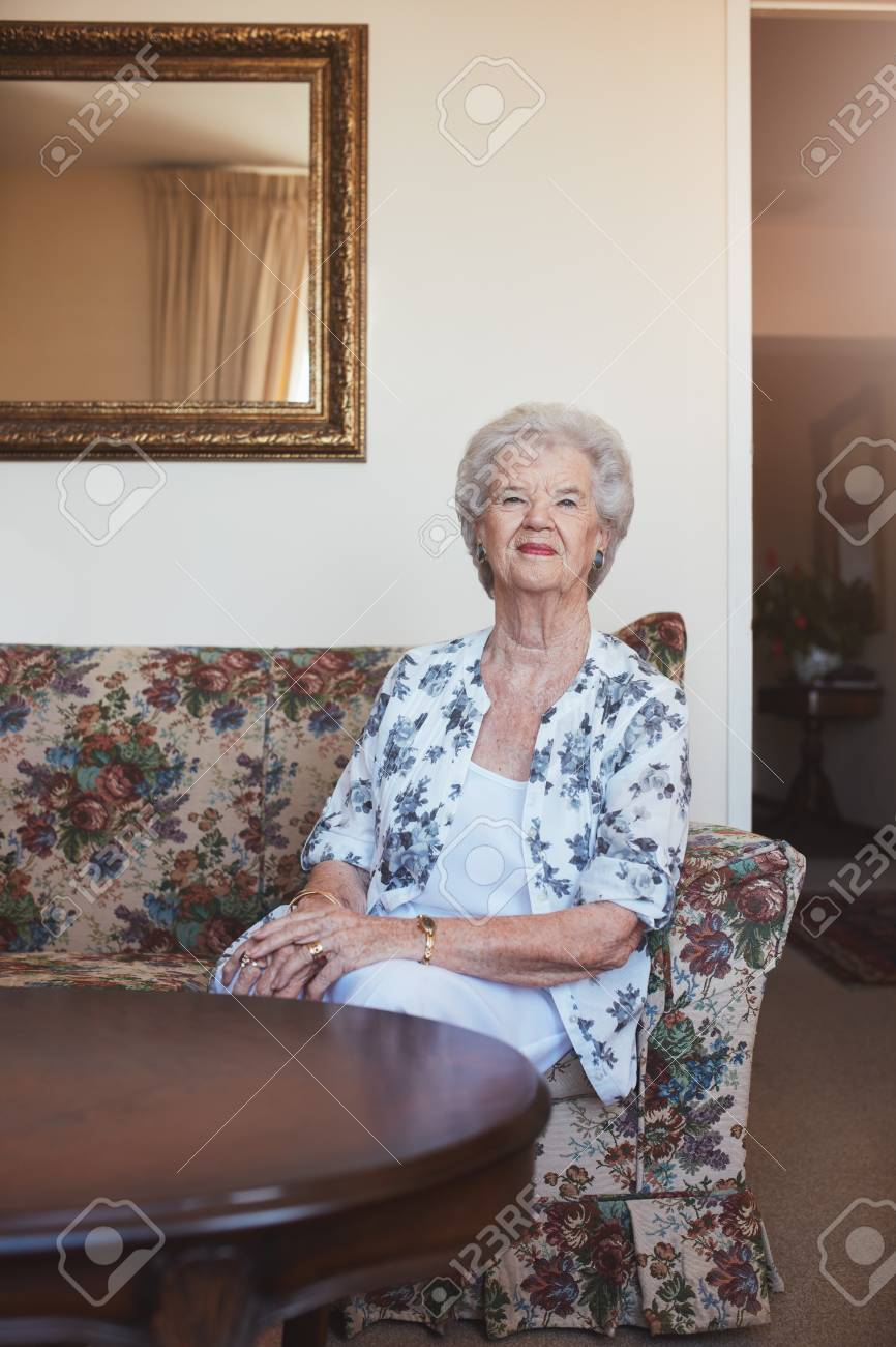 Portrait Of An Elderly Woman Sitting On A Couch At Old Age Home
