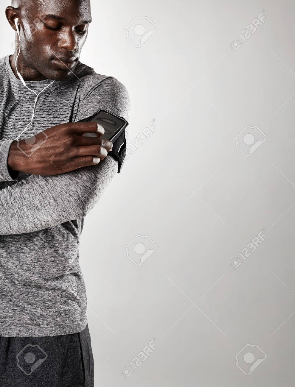 Shot of young black male model listening to music on cell phone man with mobile