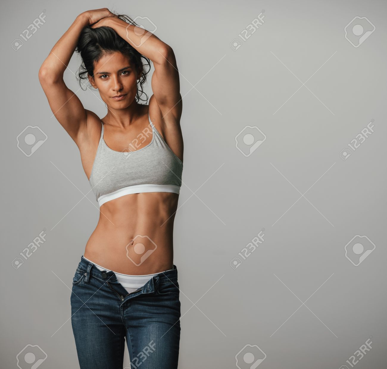Powerful athletic woman poses with arms above her head while wearing halter top and jeans - 62294076