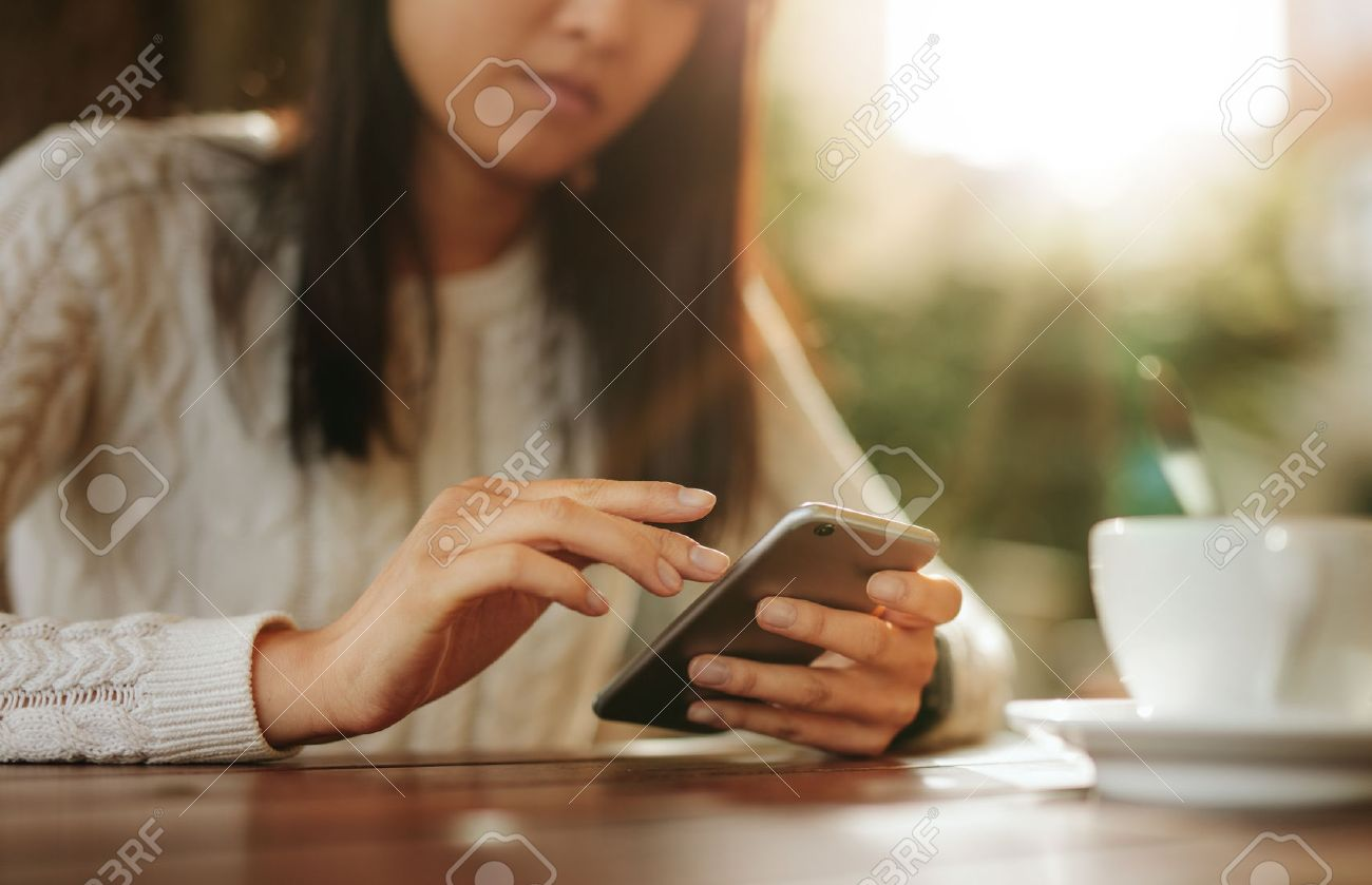 Young asian woman sitting at a table using mobile phone. Smart phone in hands of a female at outdoor cafe. - 62779109