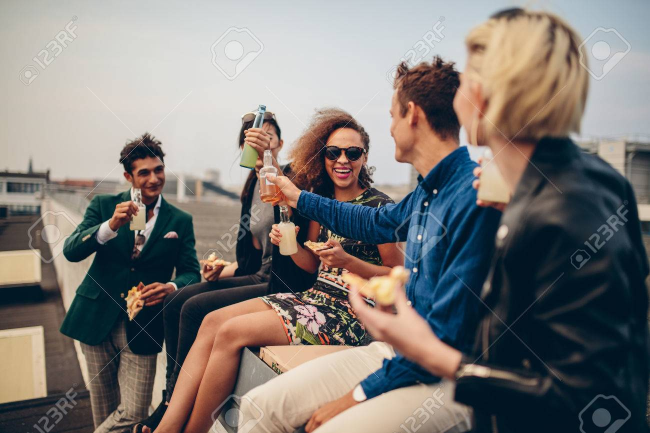 Multiethnic group of young friends partying on terrace, drinking and celebrating. Young men and women having drinks on rooftop. Foto de archivo - 64915745