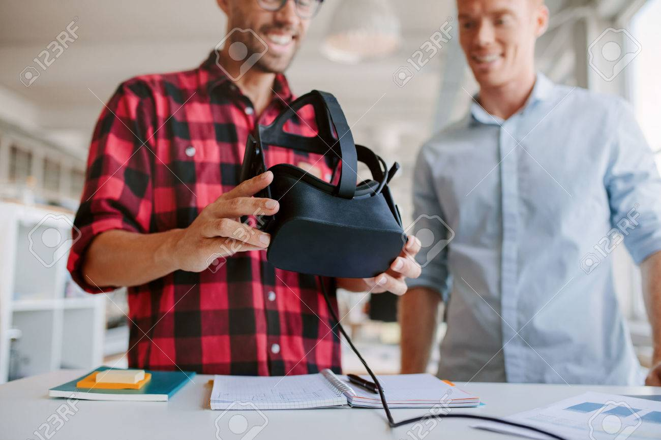 Shot of two men using virtual reality goggles in office. Business partners working in office, standing at a table with VR glasses. - 64919967