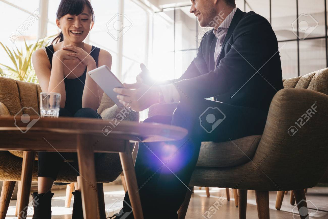 Two corporate colleagues discussing business ideas using digital tablet. Young businessman having meeting with female partner in office lobby - 64920013