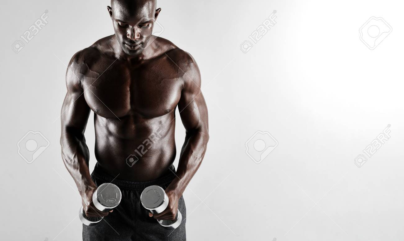 Shot of muscular young african man exercising with dumbbells fit black male model with dumbbells