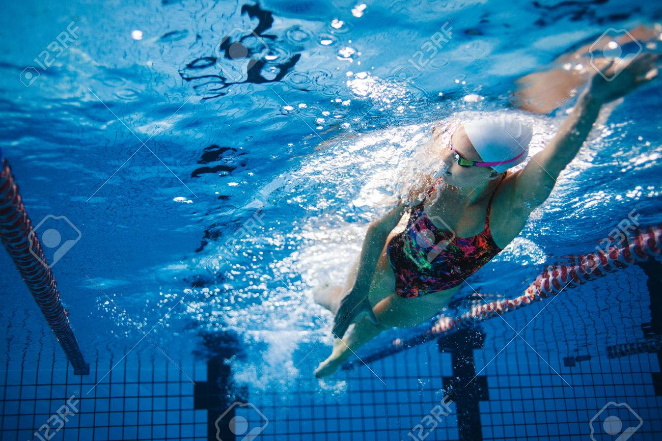 Underwater shot of fit swimmer training in the pool. Female swimmer..