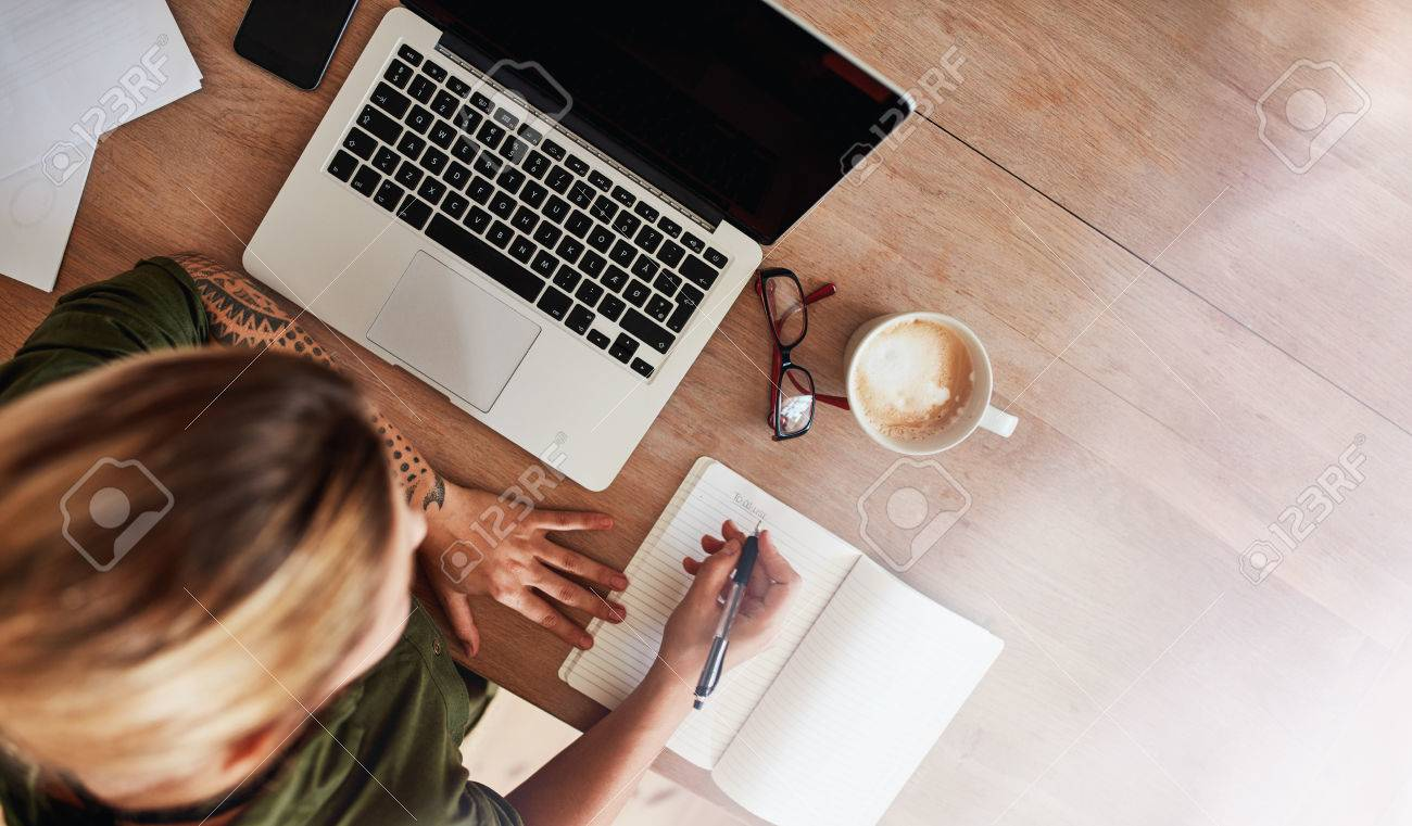 top view shot of woman sitting at table with laptop and coffee