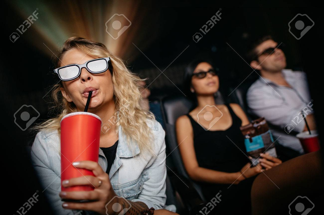 76facd784ca Stock Photo - Young woman having cold drink wearing 3d glasses and watching  movie in theater. People in cinema watching 3d film.