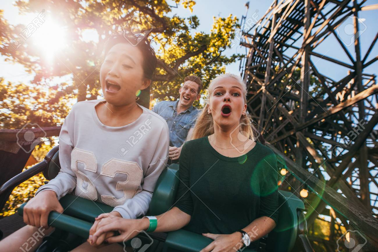 Shot of young friends enjoying riding roller coaster at amusement park. Young people having fun on rollercoaster. - 127406224