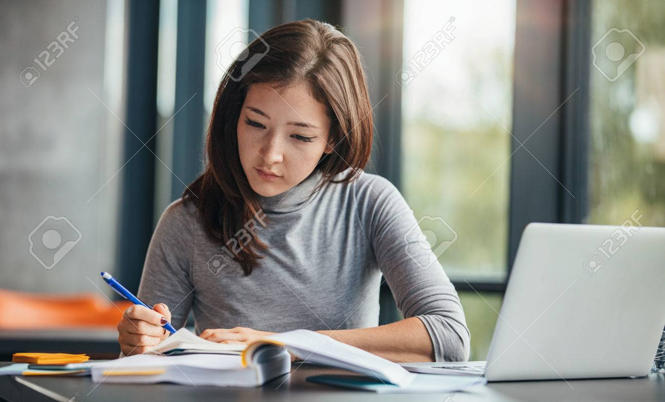 Shot of young woman taking down notes in diary. Female university student preparing note for the exam at library. - 67081268