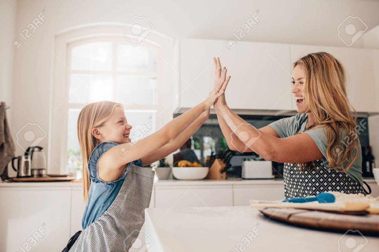 Little girl and her mother in kitchen giving high five. Mother and daughter in kitchen cooking. - 68310051