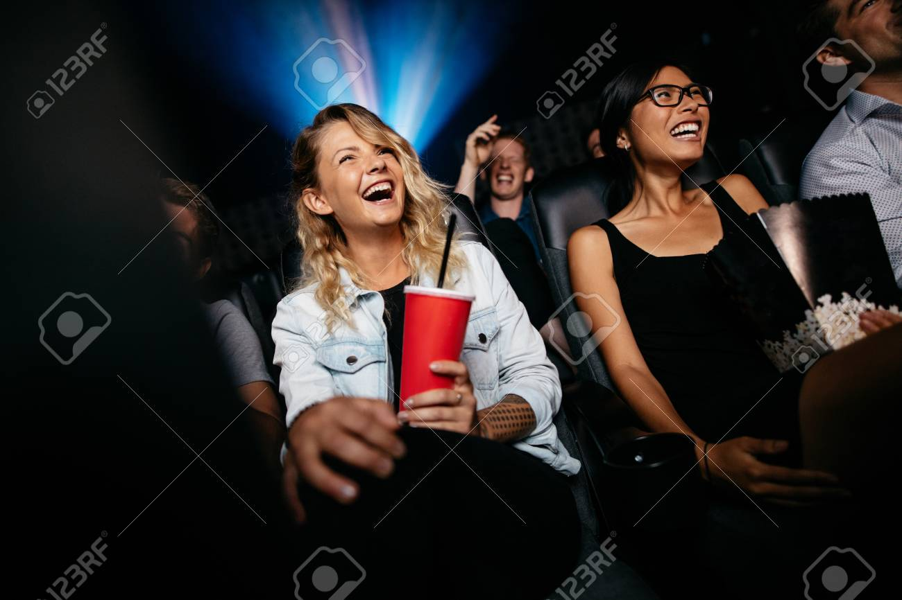 Young people laughing while watching film in movie theater. Group of friends in multiplex cinema with drinking and popcorn. - 69793352