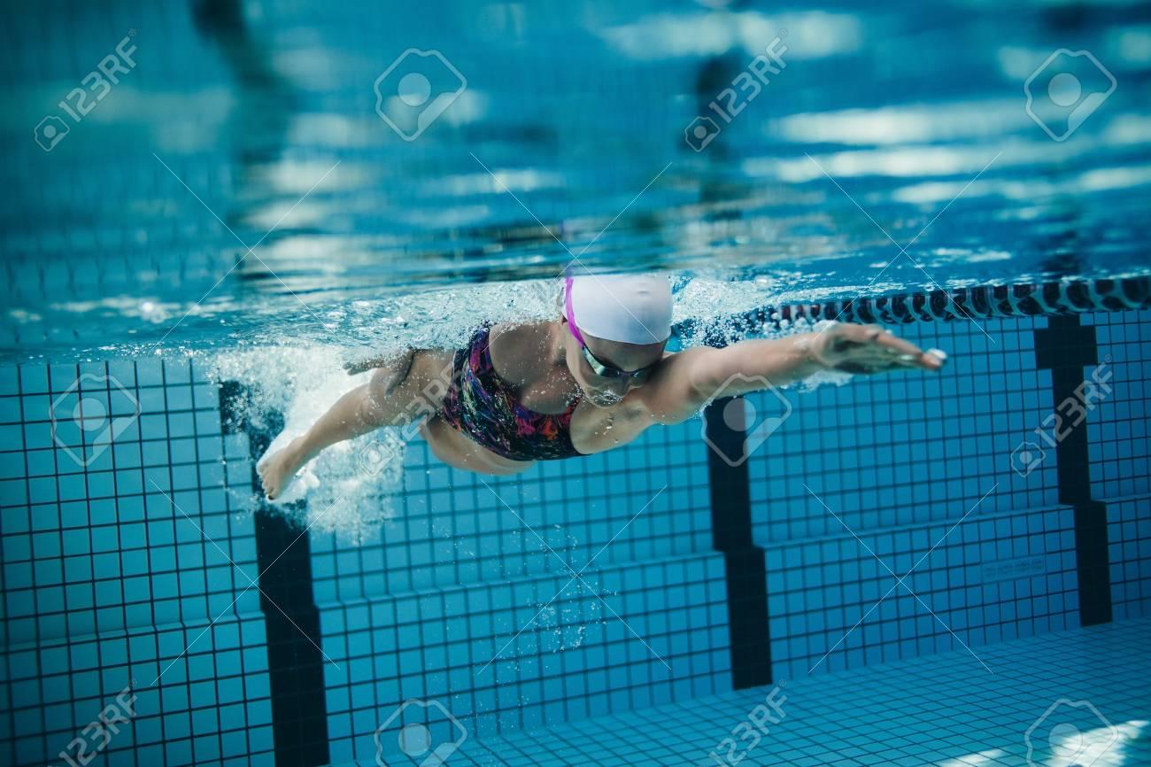 Underwater shot of female swimmer in action inside swimming pool