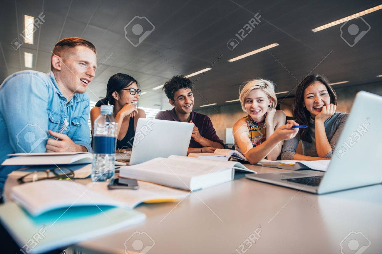 University students sitting together at table with books and looking at laptop. Happy young people doing group study in library. - 70199366