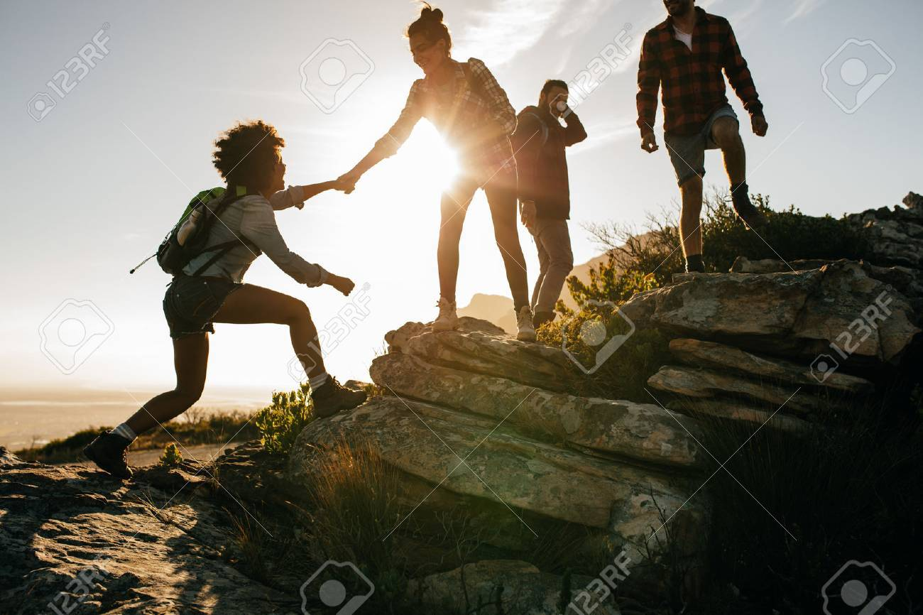 Group of hikers on a mountain. Woman helping her friend to climb a rock. Young people on mountain hike at sunset. - 71836814
