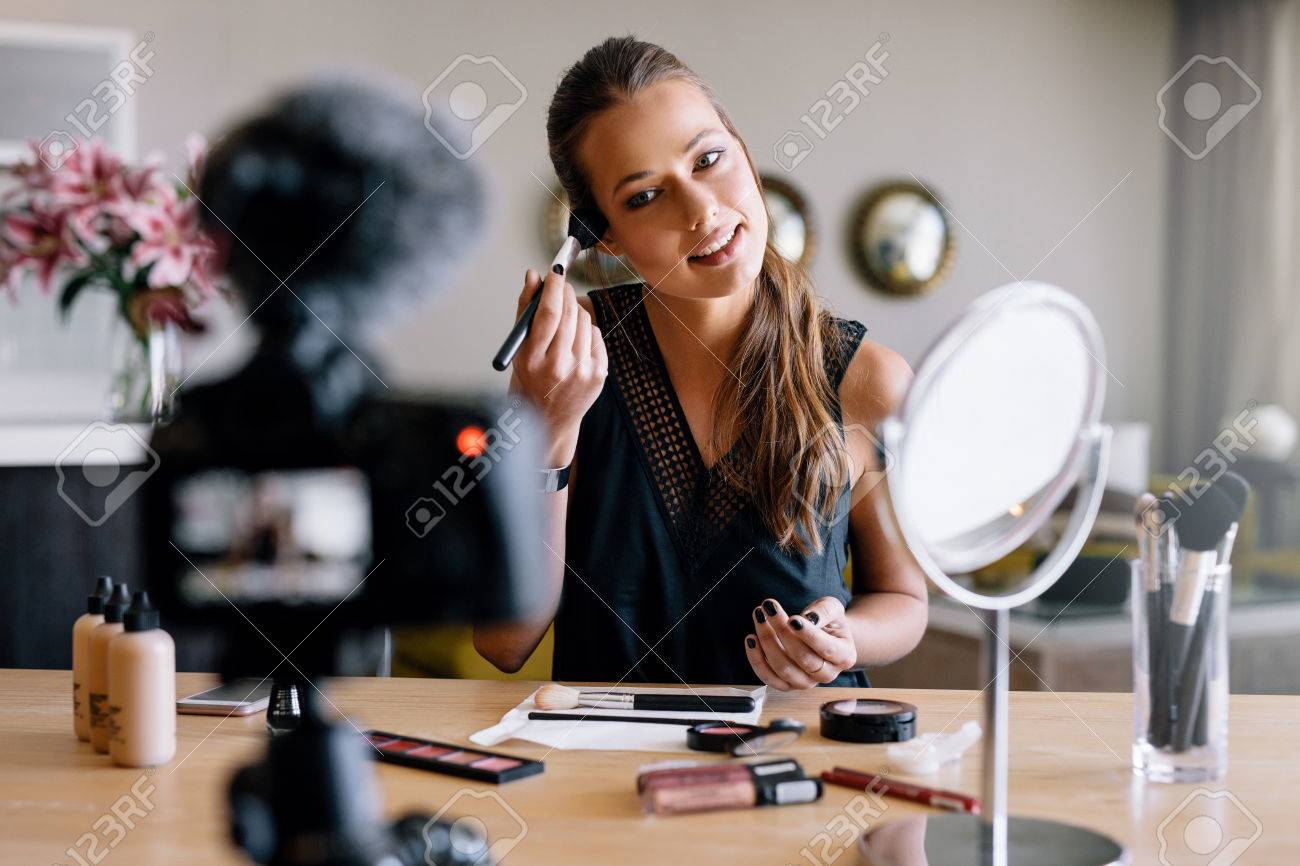 Young lady recording her video while applying cosmetics. Woman making a video for her blog on cosmetics. - 74642568