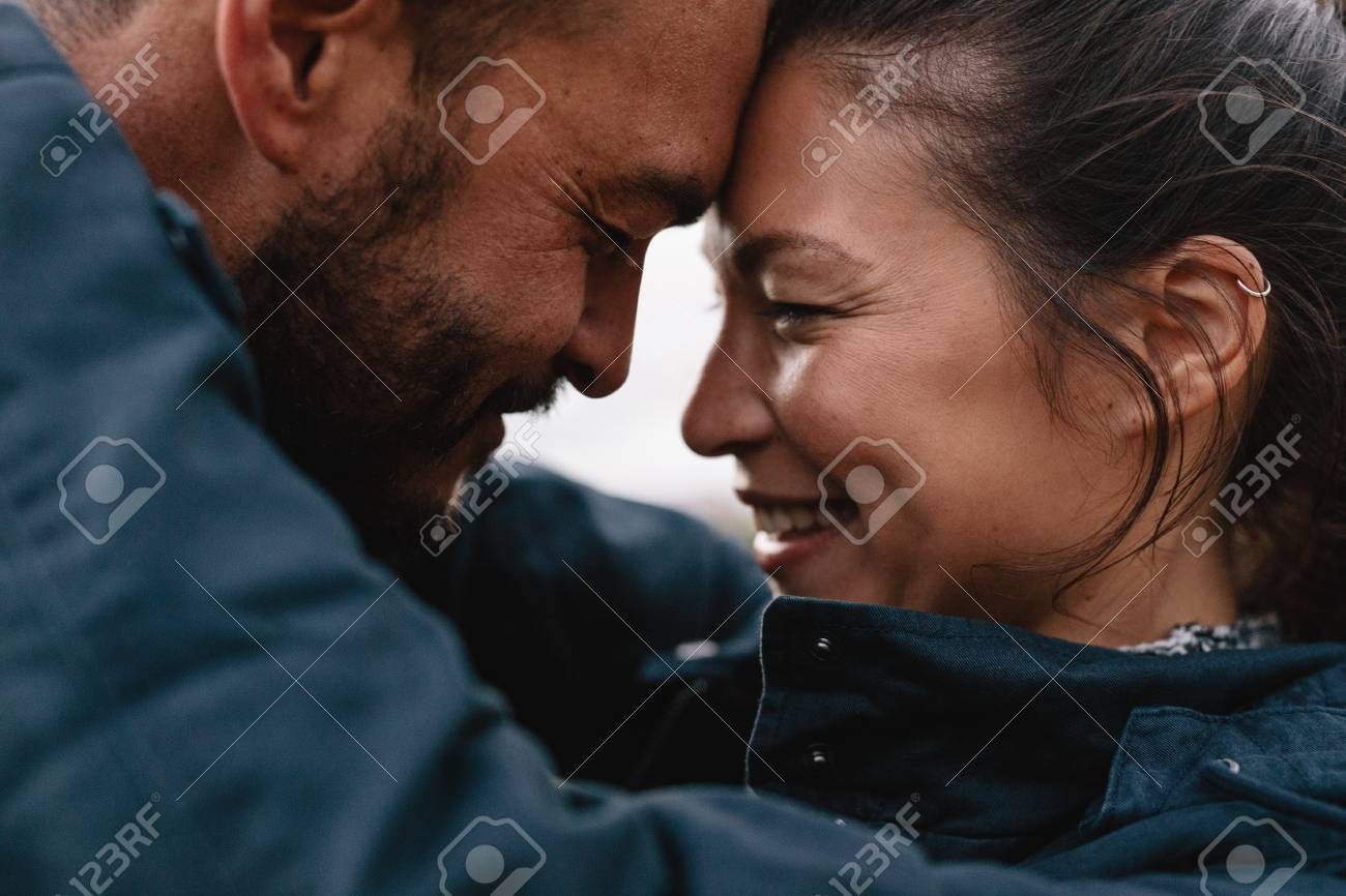 Close-up side portrait of young mixed race couple in love. Romantic couple embracing each other and smiling. - 77980639