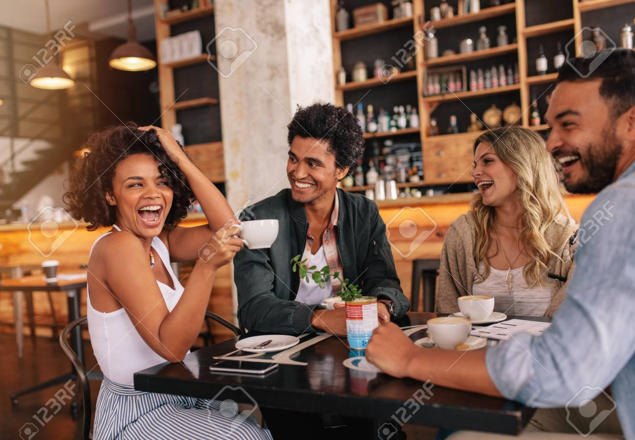 Happy Young People Sitting Around Cafe Table And Drinking Coffee Stock Photo Picture And Royalty Free Image Image 78529098