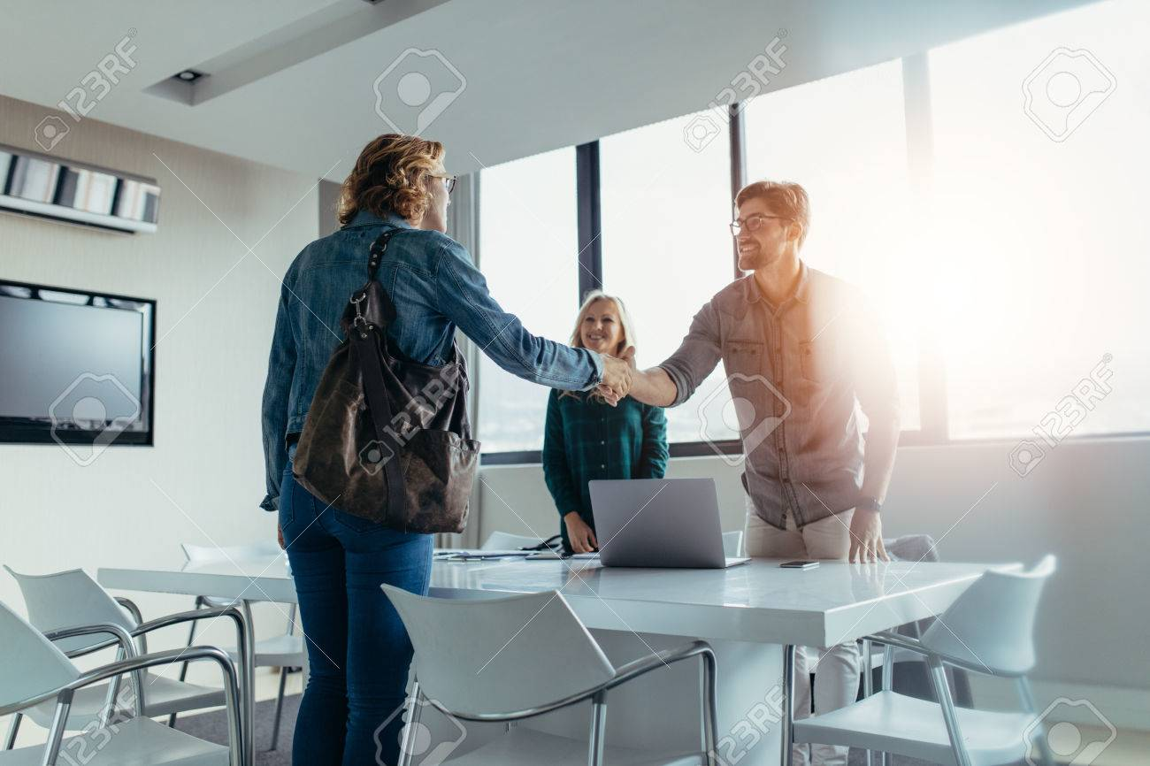 Business people finishing up a meeting. Man shaking hands with female client after successful deal. - 82510602