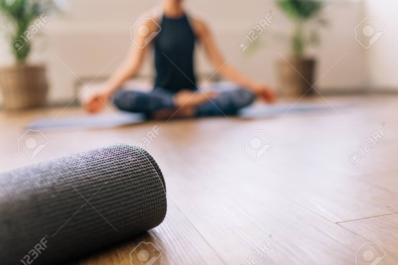 Close Up Of Rolled Yoga Mat In Fitness Center And Blurred Woman Stock Photo Picture And Royalty Free Image Image 87606755