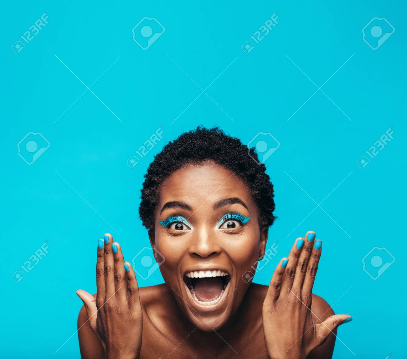 Excited Young Woman With Vibrant Eye Shadow And Nail Paint Female Model Showing Her Vivid