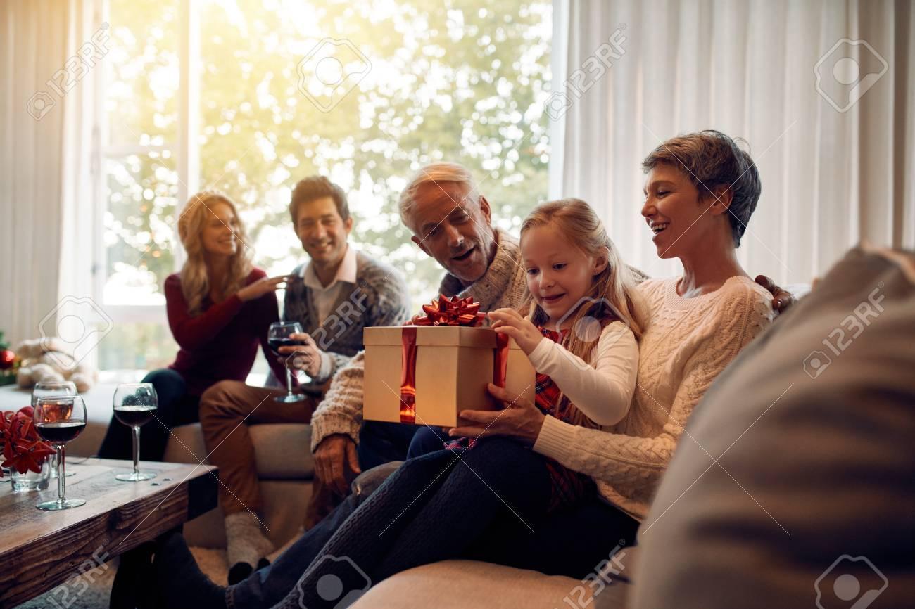 Niña Sentada En La Sala De Estar Con La Familia Abriendo Regalos De