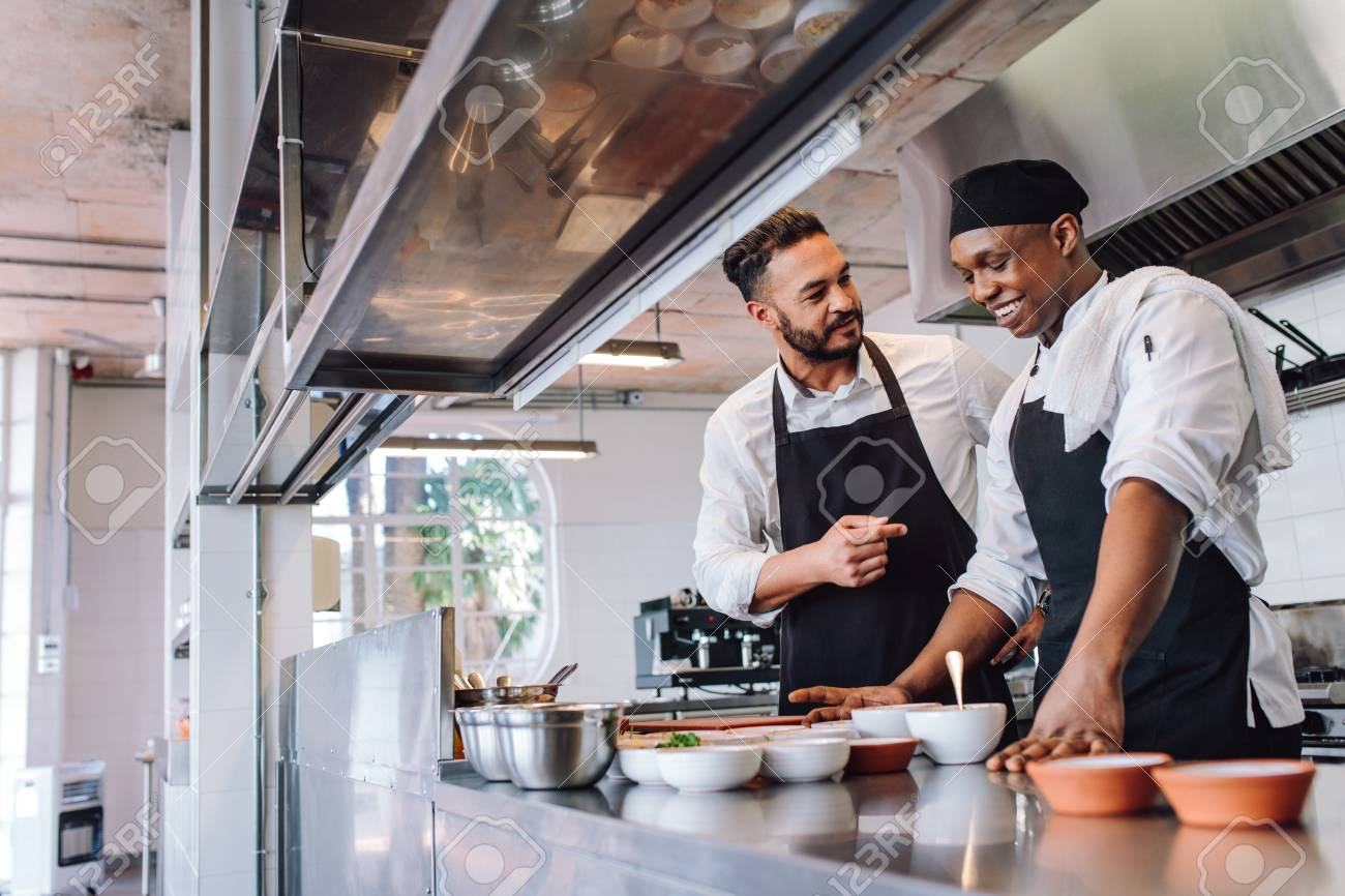 Happy Men Chefs Cooking Food At Cafe Kitchen Two Cooks Making Stock Photo Picture And Royalty Free Image Image 89704613