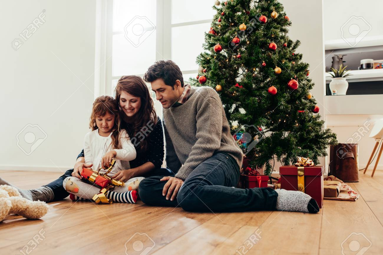 small and happy family unboxing gifts sitting beside a christmas tree young couple watch their