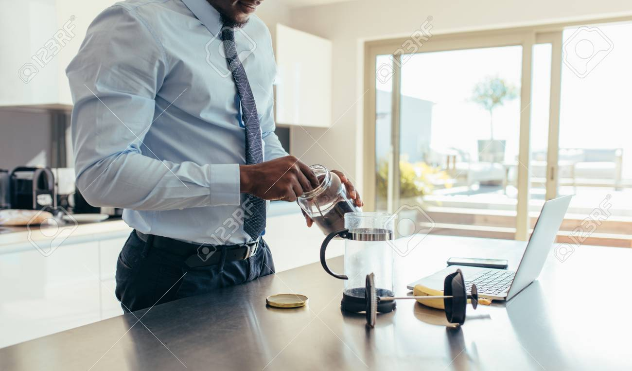 Man in formal clothes making coffee using French press with a..