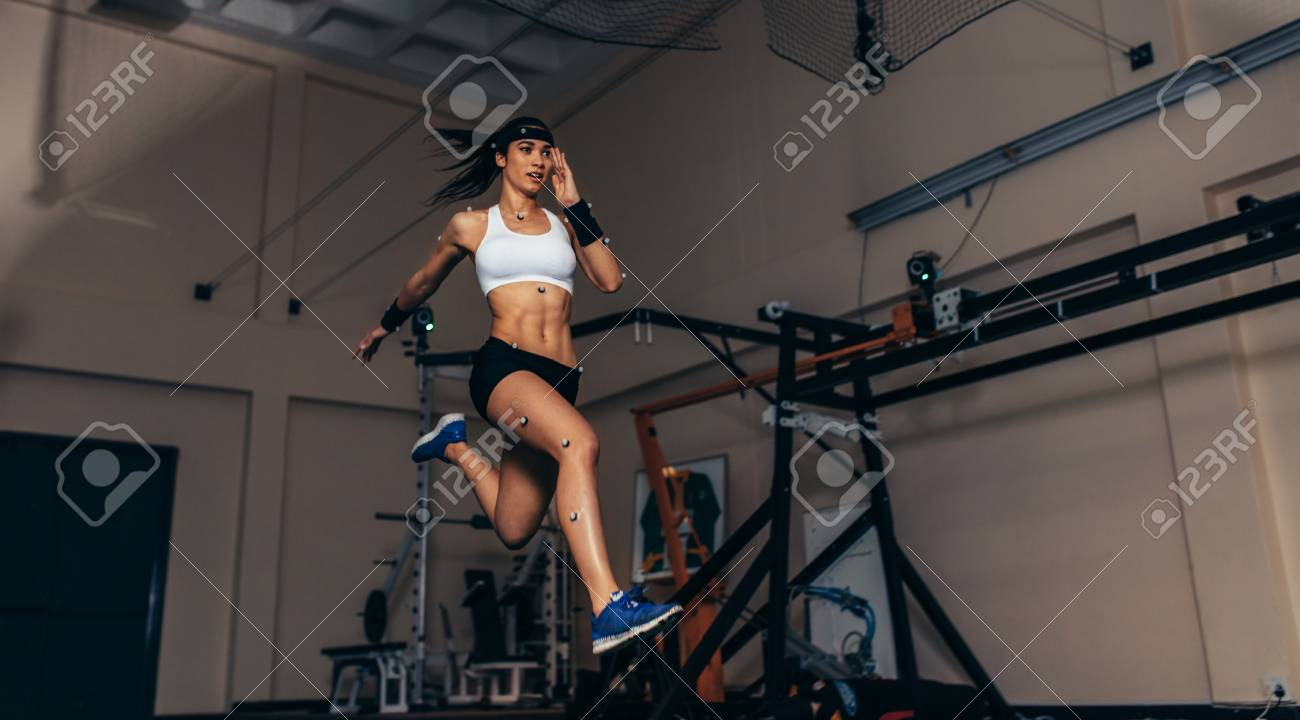 Female athlete with motion capture sensors on her body running in biomechanical lab. Recording the movement and performance of sportswoman in sports science lab. - 91084957