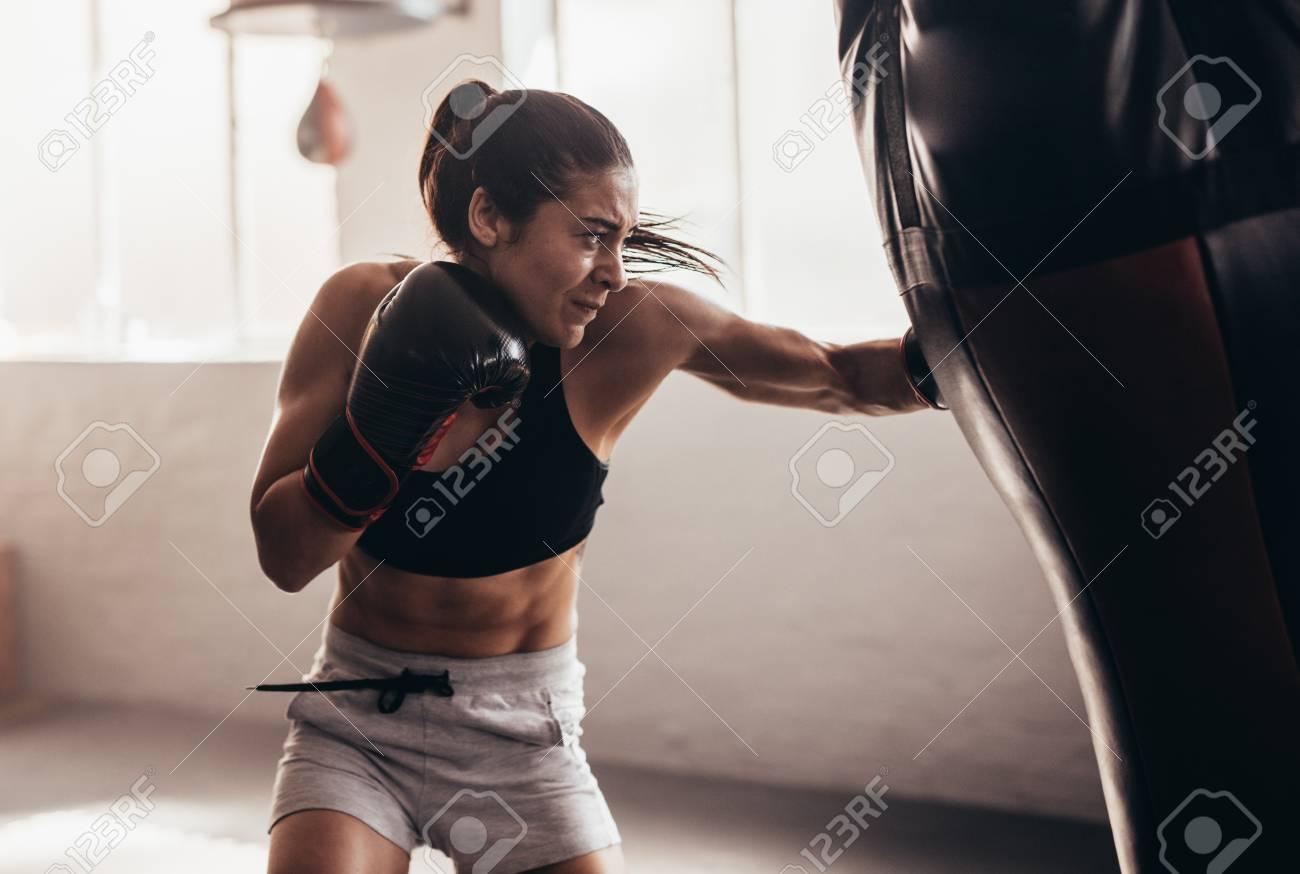 Female boxer hitting a huge punching bag at a boxing studio. Woman boxer training hard. - 91758375