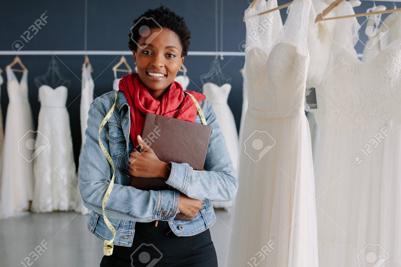 Portrait of wedding dress store owner with a diary. Woman dressmaker in her bridal boutique. - 93156073
