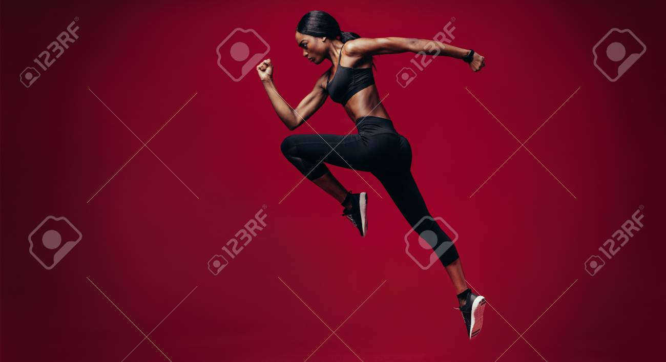 Sports woman running over red background. Full length shot of healthy young african woman sprinting. - 93156167