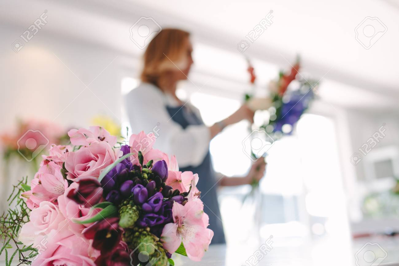 Colorful Flower Bouquet On Counter With Female Florist Working ...