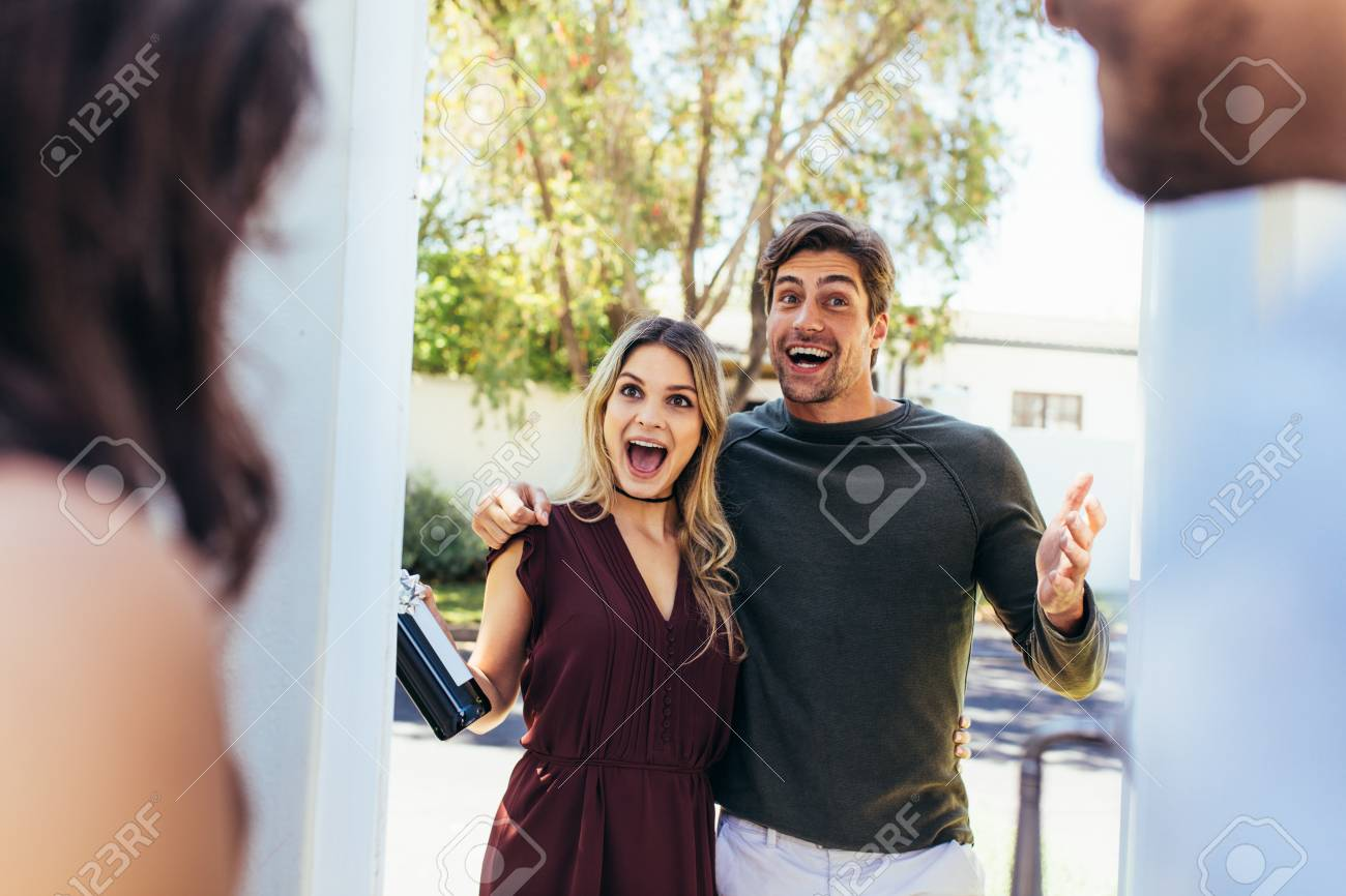 Excited couple at entrance door with bottle of wine. Friends being welcomed by couple at the door. Attending friend's housewarming party. - 94202584