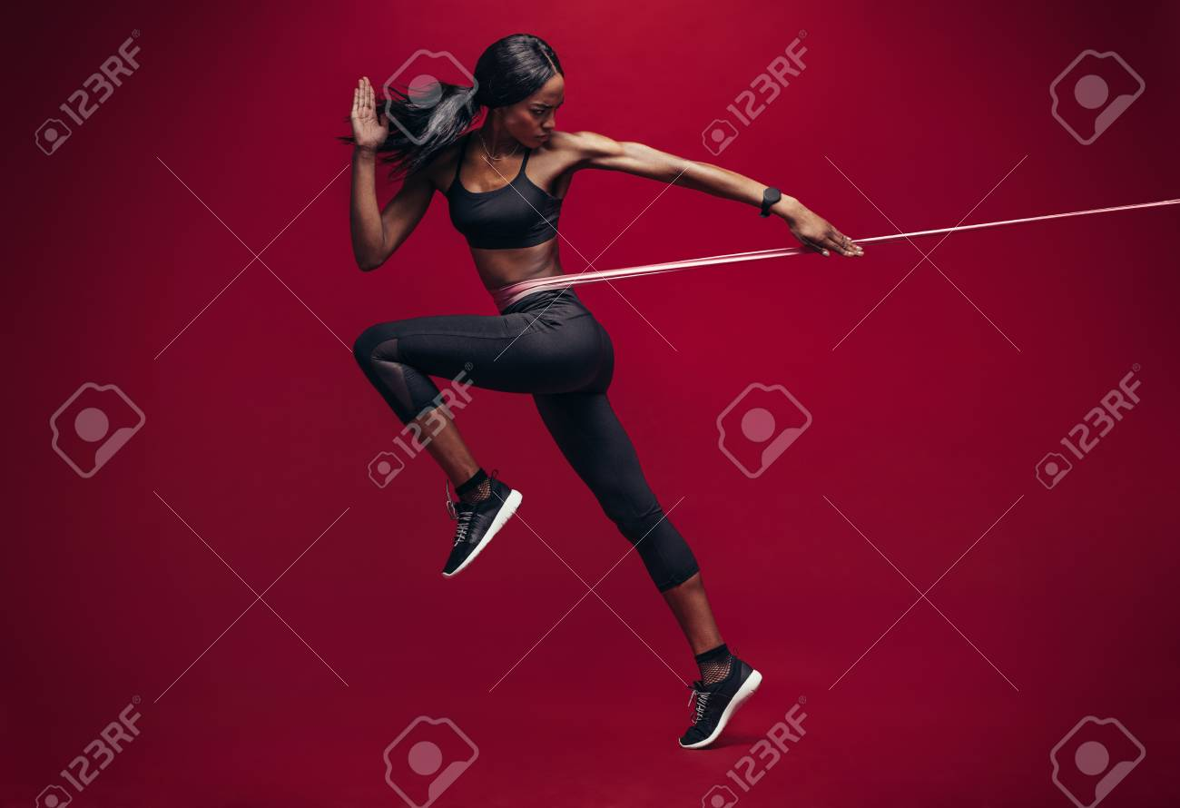 Sporty woman exercising with resistance band on red background. African female athlete working out with elastic bands in studio. - 94183791