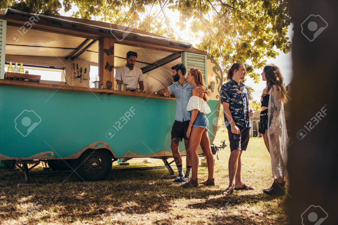 Young people buying street food from a food truck at park. Group of men and woman at food truck. - 103040183