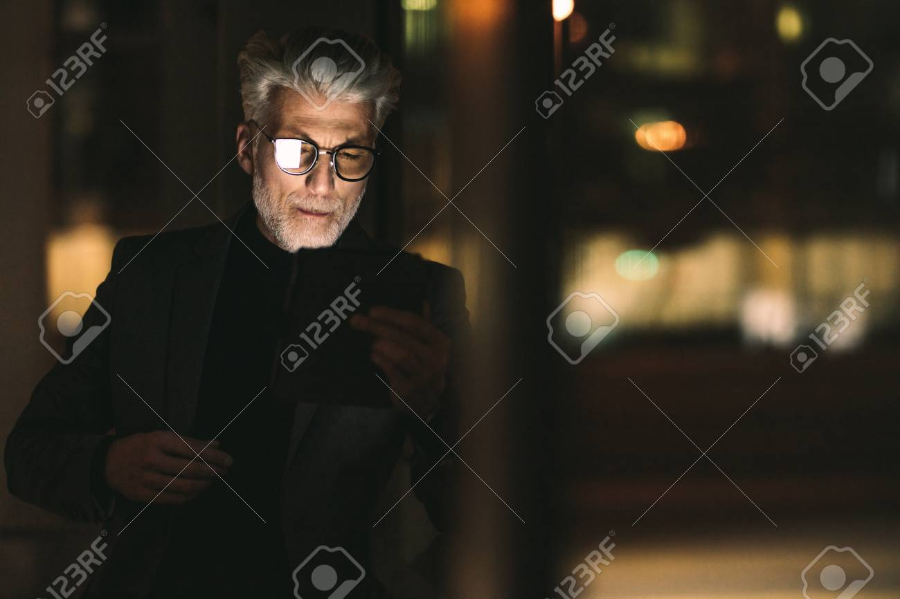 Senior businessman looking at digital tablet in office. Mature man during  late working hours in