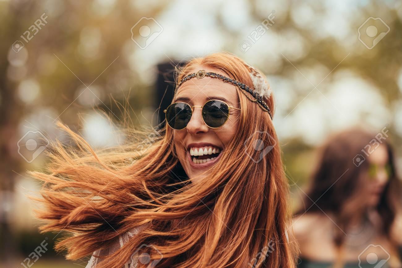Caucasian woman in retro look enjoying at music festival. Beautiful young woman smiling in sunglasses at park. - 107259468