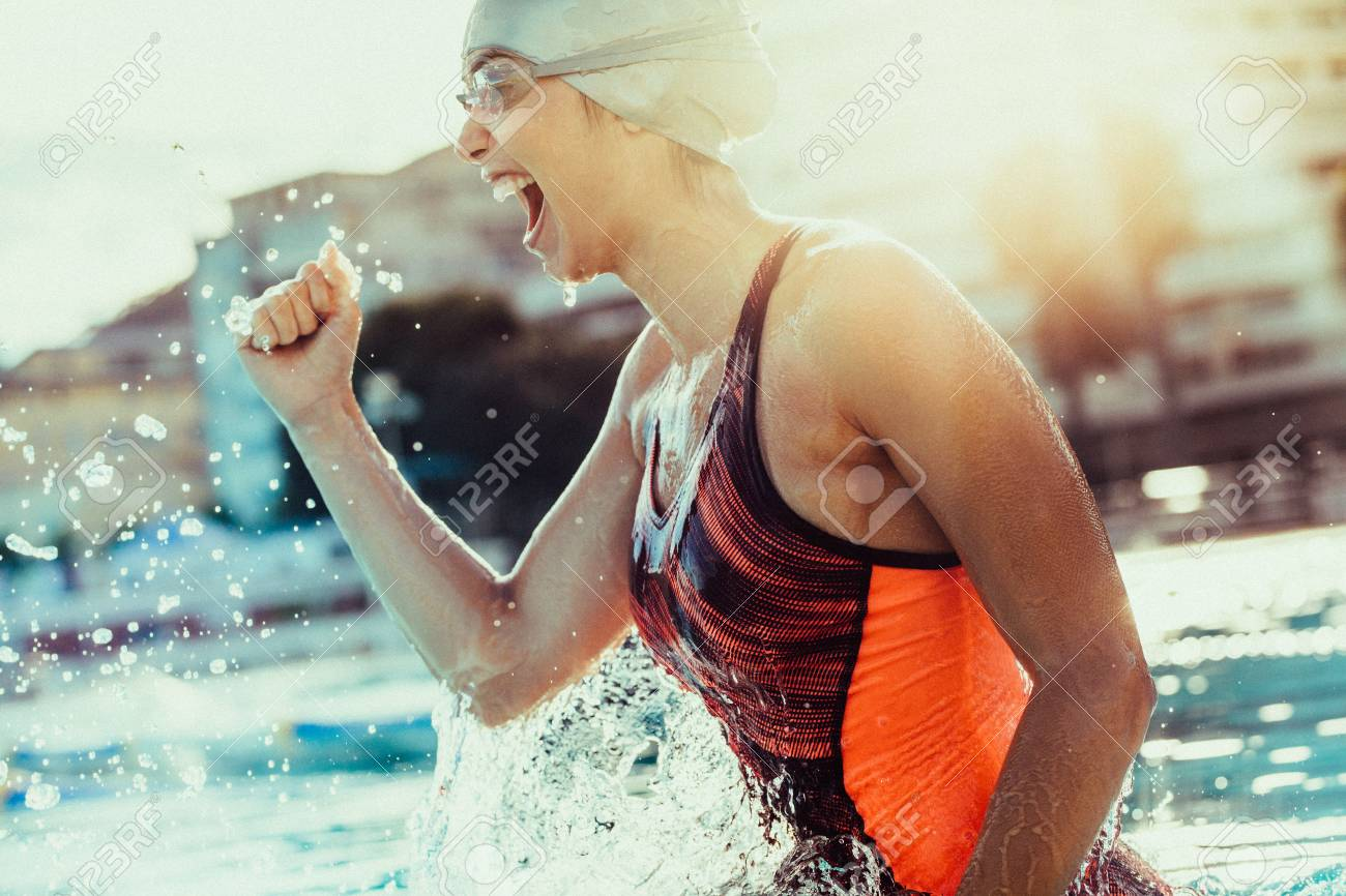 Excited female swimmer with clenched fist celebrating victory in the swimming pool. Woman swimmer cheering success in pool wearing swim goggles and cap. - 111938990