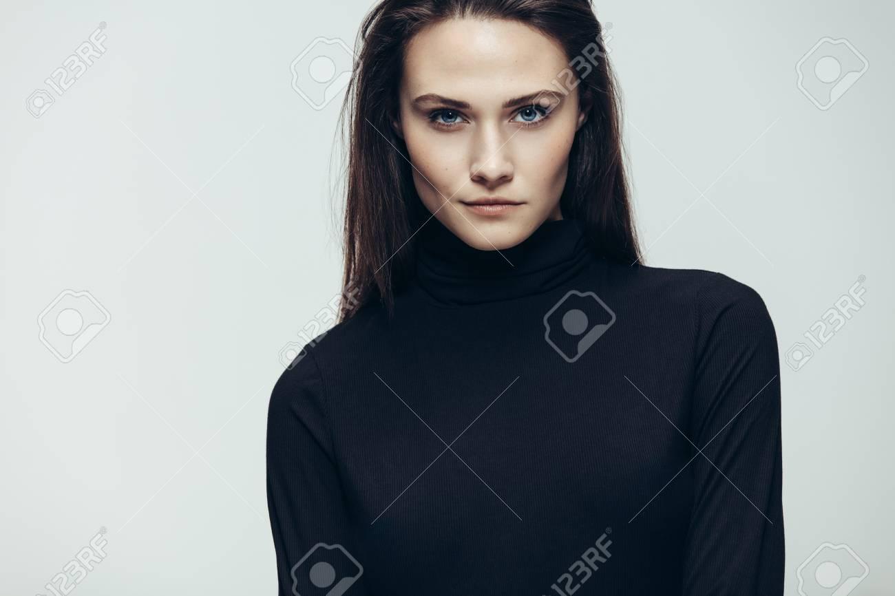 Cierre de mujer joven imponente en vestido negro mirando a la cámara. modelo  femenino en 5ed5c62767
