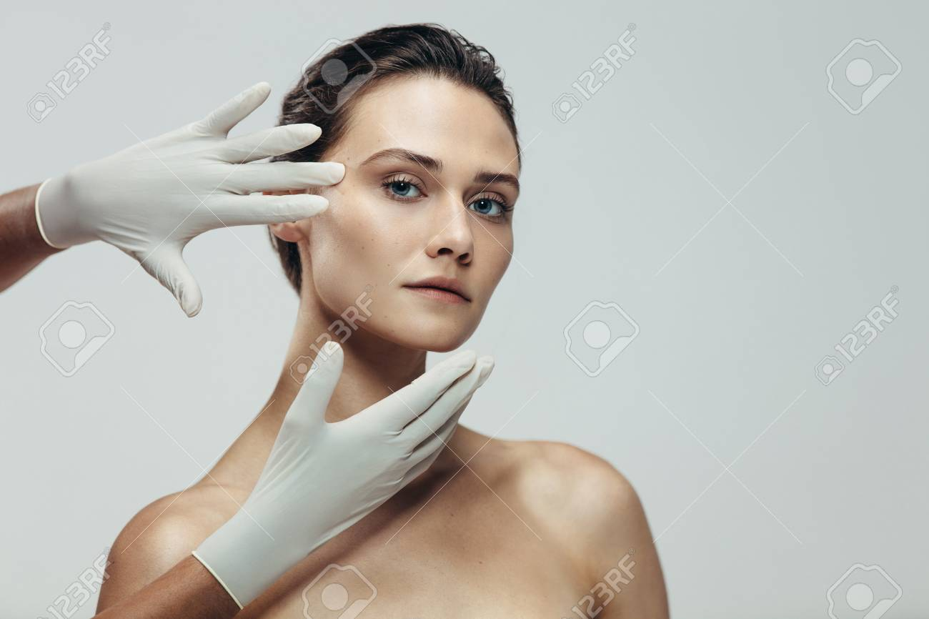 Beautician hands with gloves touching beautiful woman face before plastic surgery. Female standing against grey background with a cosmetologist touching her face. - 109099636