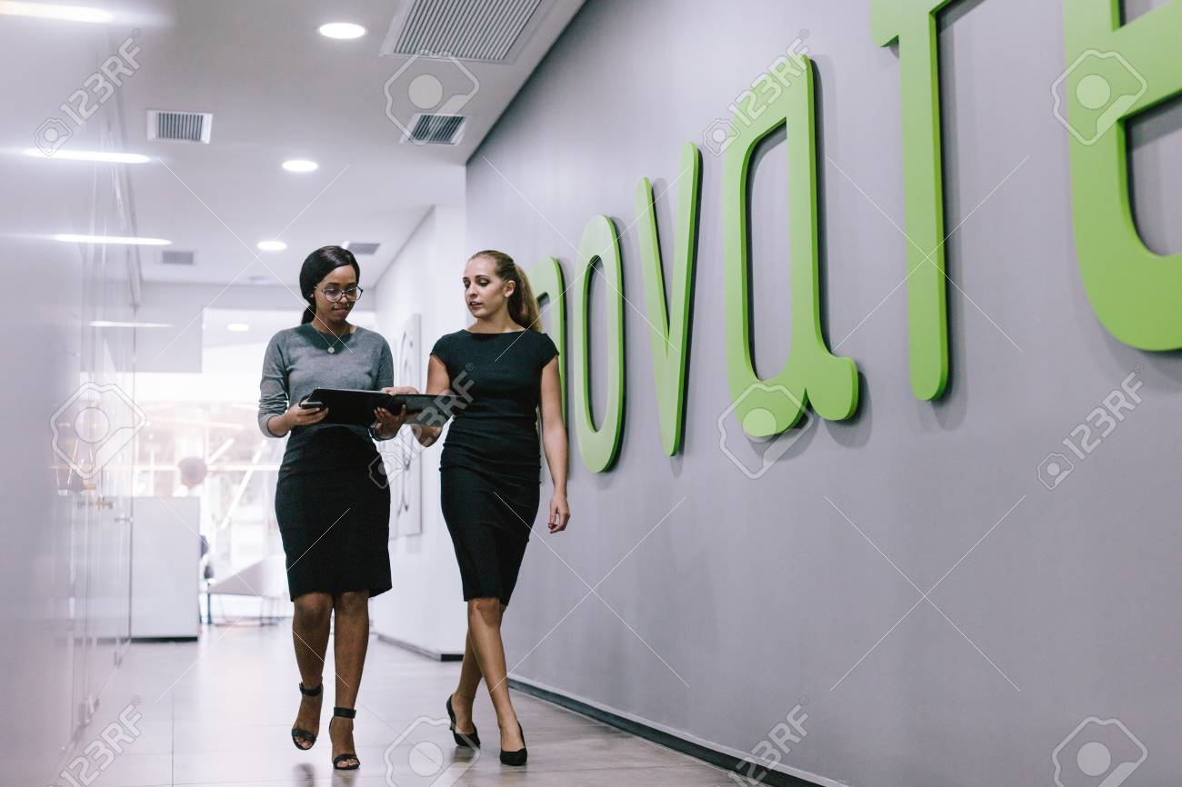 Two business women walking through office corridor and looking at a file. Business professionals discussing work in modern office hallway. - 111959337