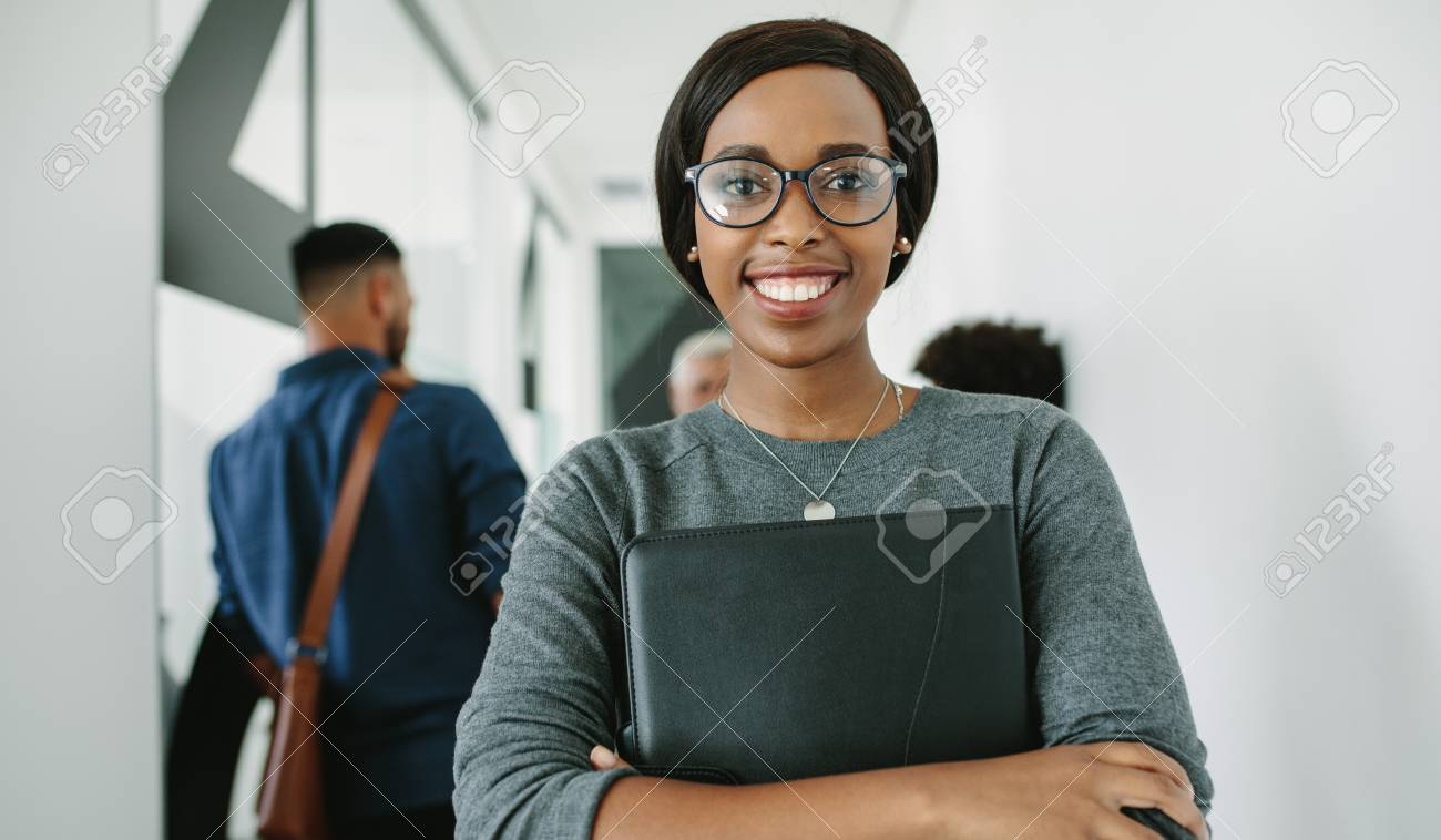 Portrait of cheerful african businesswoman wearing glasses standing in office with team in background. Smiling female executive with folder in office hallway with coworkers talking at the back. - 113598179